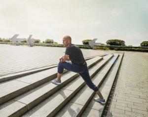Mann bei Dehnuebungen auf Treppe in Stuttgart